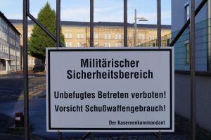 """Foto des Schildes """"Militärischer Sicherheitsbereich. Unbefugtes Betreten verboten! Vorsicht Schußwafffengebrauch! Der Kasernenkommandant""""eines Eingangsbereiches (Reuterstr.) der Ermekeilkaserne"""
