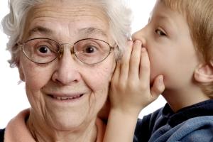 Foto von Jungem, der älterer Frau etwas ins Ohr flüstert