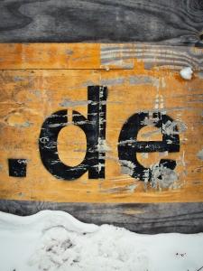 Foto der auf einem Holzbrett aufgemalten Top-Level-Domain-Endung .de