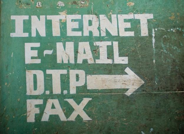 """Foto einer Wandbeschriftung: """"Internet, E-Mail, D.T.P, Fax"""" mit Pfeil nach rechts"""