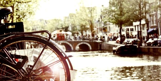Foto von einer Gracht in Amsterdam mit dem Hinterrad eines Fahrrades im Vordergrund