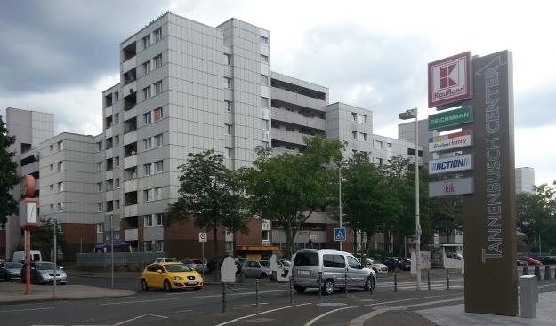 Foto von Gebäuden und einer befahrenen Straße vor einer Werbesäule des Tannenbusch-Center in Bonn-Tannenbusch am 15.7.2017