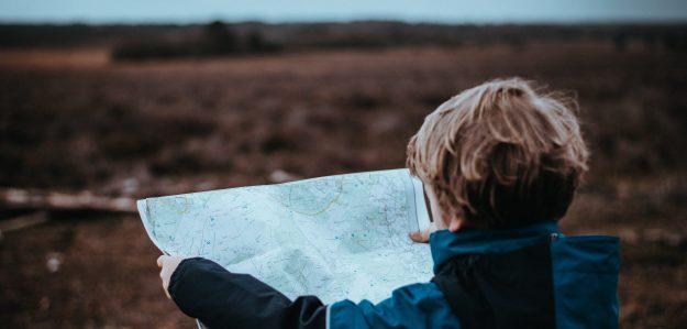 Foto eines Kindes, dass eine Karte vor einer undefinierten Landschaft hält