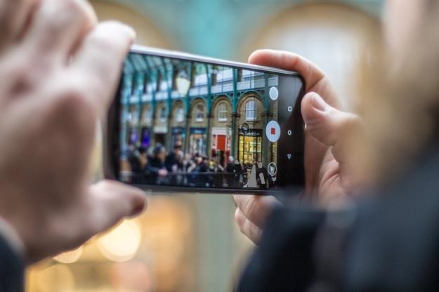 Foto eines Handys, mit dem ein Foto von einer Stadtszene gemacht wird