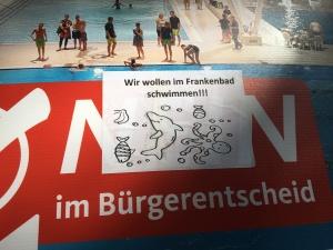Foto eines Aufklebers auf einem Plakat von CDU, Bündnis90/Die Grünen und FDP zum Bürgerentscheid über ein neues Schwimmbad in Bonn
