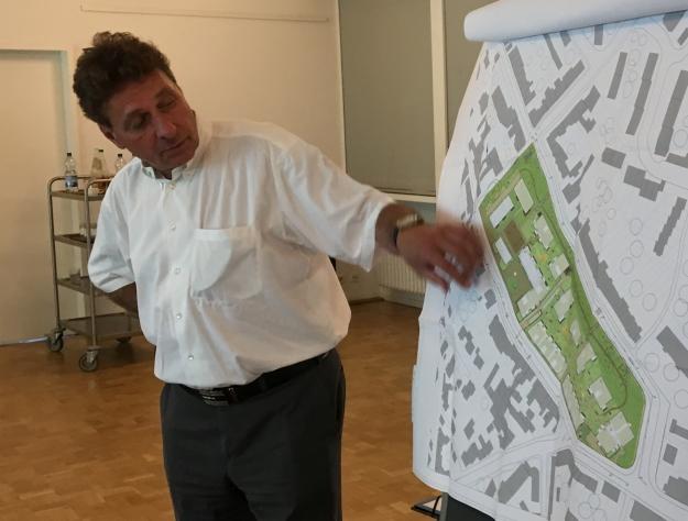 Foto von Dirk Baarz vom Eigentümer und Entwickler Instone Real Estate, wie er anhand eines Plans das Projekt erläutert