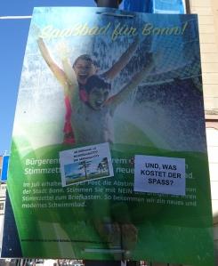Foto von Aufklebern von Unbekannten auf einem Plakat von Horst Burbulla zum Bürgerentscheid über den Stop des Baus eines neuen zentralen Bades in Bonn.