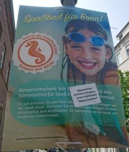 Foto eines Aufklebers von Unbekannten auf einem Plakat von Horst Burbulla zum Bürgerentscheid über den Stop des Baus eines neuen zentralen Bades in Bonn.