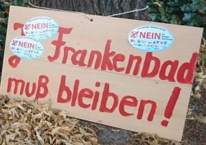 Foto eines selbstgemachten und mit Aufklebern beklebten Schildes zum Bürgerentscheid über den Stop des Baus eines neuen zentralen Bades in Bonn.