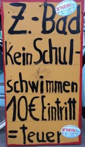 Foto eines Plakates eines/einer unbekannten Künstler*in zum Bürgerentscheid über den Bau eines zentralen Schwimmbades in Bonn