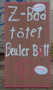 Foto eines Schildes eines/einer unbekannten Künstlers/Künstlerin zum Bürgerentscheid zum Neubau eines zentralen Bonner Bades - mit Aufklebern der Gegenseite