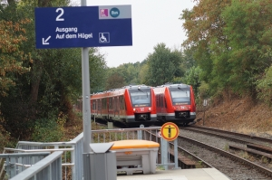 """Foto des Bahnsteig-Ausgangsschildes """"Auf dem Hügel"""" auf dem Bahnsteig Bonn Endenich-Nord mit ein- und ausfahrenden S-Bahnen nach Bonn Hbf und Bad Müstereifel"""