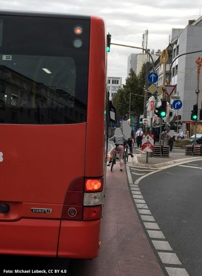 Foto der völlig unzureichenden Fahrradspur am Bertha-von-Suttner Platz in Bonn, mit Bus nahe an Radfahrer*innen